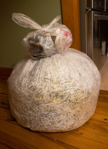 Stacked bags of trash, the lower one containing shredded documents.