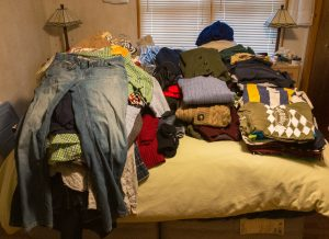 Piles of clothing covering a bed.